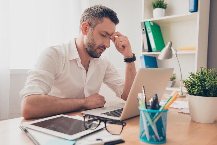 Tired man working on healing negative mindsets at work