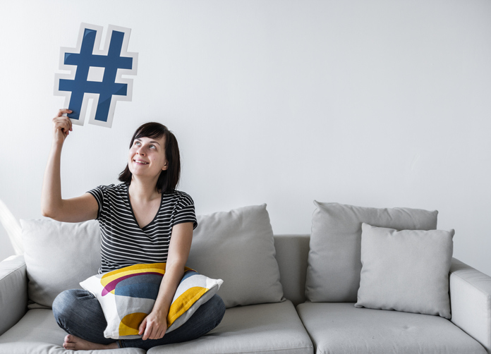 Woman holding up a hashtag symbol.