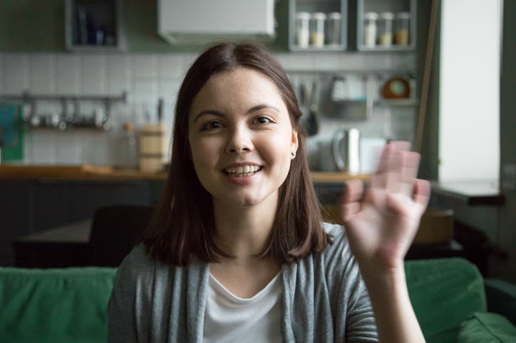 Woman raising her hand that she's excited about starting a coaching business.